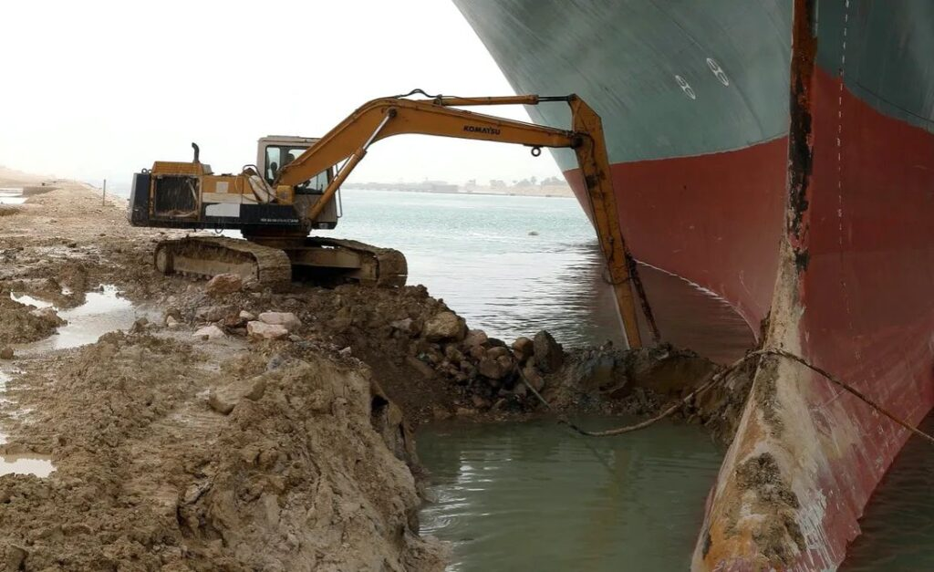 excavator trying to free a container ship stuck across suez canal